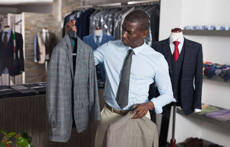 Afro-american man purchaser trying jacket in the dress shop