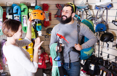 Young couple buying climbing equipment in store Stock fotó