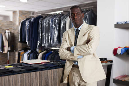 Portrait of afro-american man costumer trying business style jacket in the shop Stock fotó
