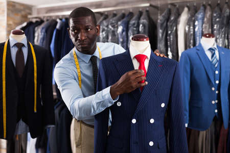 Afro-american man seller is showing jacket and tie in shop Stock fotó