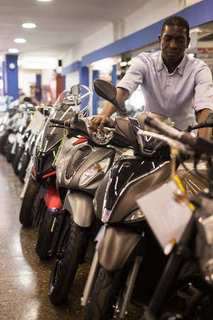 Afro american man is shopping and choosing new motobike in moto store