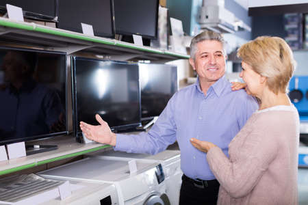cheerful husband and wife choose for themselves TV in center of electronics