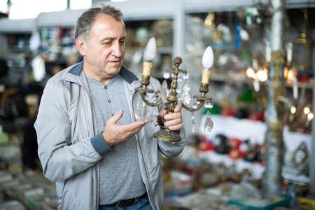 Joyful middle aged man buying retro handicrafts 版權商用圖片