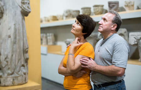 Mature couple is looking at the exposition in museum