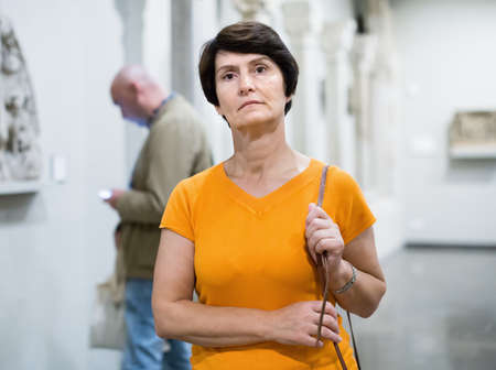 Mature female tourist is looking at the exposition