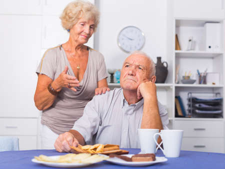 Senior woman asking for forgiveness from offended husband