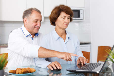 Smiling mature family couple using laptop together at kitchen table