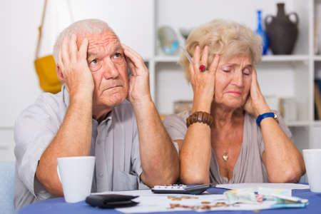 Worried mature man and woman analyzing bills