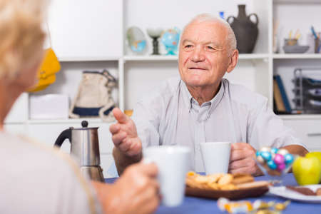Smiling elderly man drinking tea and talking with woman
