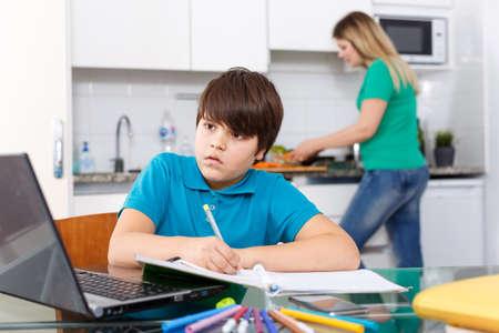 Boy doing homework, mother cooking Banque d'images
