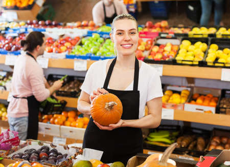 Saleswoman offering pumpkin in supermarket