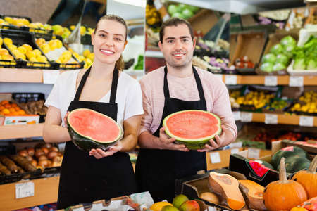 Young saleswoman and salesman holding half of watermelon in hands in fruit store 免版税图像
