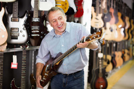 Man musician is playing on wooden electric guitar