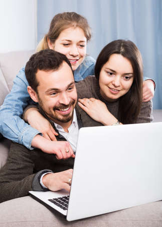Family members enjoying booking hotel online on laptop together at home