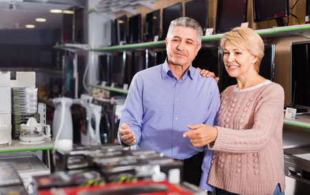 Adult married couple looking at and choose home appliances
