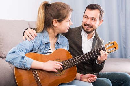 Guitar tutor helping client learn instrument
