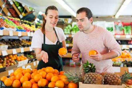 Young woman wearing apron selling fresh oranges to man customer