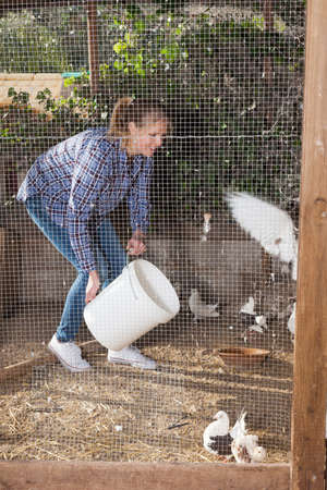 Woman feeding pigeons in aviary