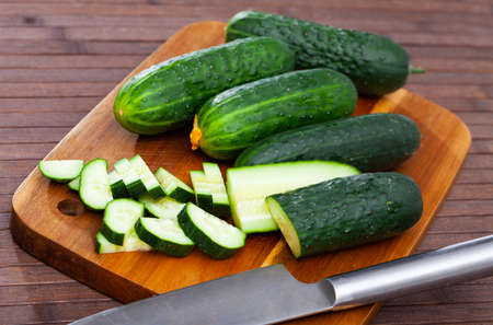 Many ripe juicy cucumbers on wooden surface