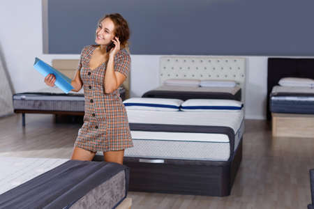 Young attractive woman talking on phone while choosing new mattress in home furnishings store
