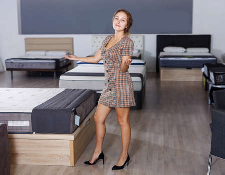 saleswoman demonstrating assortment of mattress