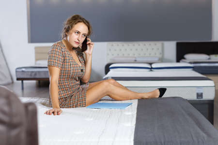 Woman talking on phone in mattress store 免版税图像