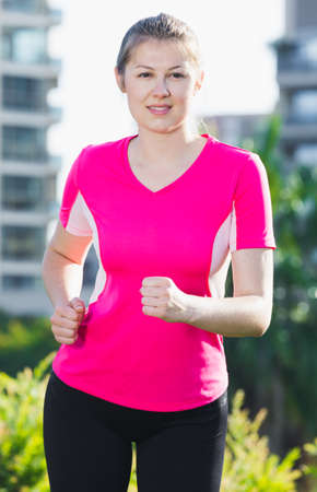 Young girl in pink T-shirt is jogging