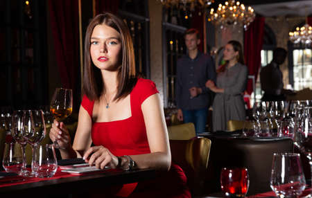 Attractive woman in red dress is expecting man for dinner in luxury restaurante Banque d'images