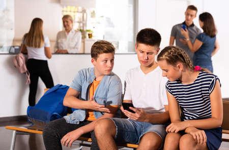 Schoolmates with smartphones in college