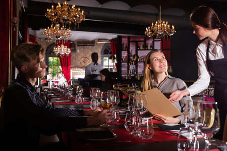 Friendly smiling female waiter bringing order to visitors in luxurious restaurant