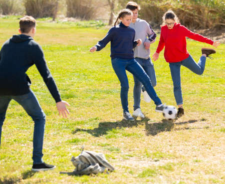Teenagers playing football outdoors