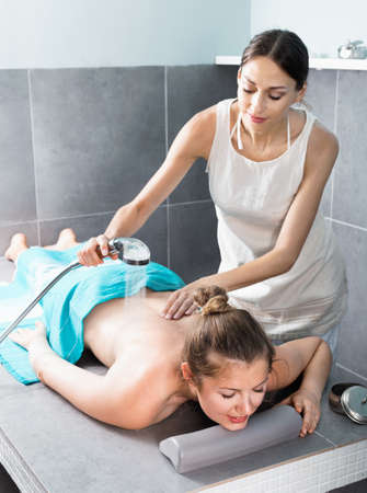 Professional beautician performing procedure body scrubbing to girl