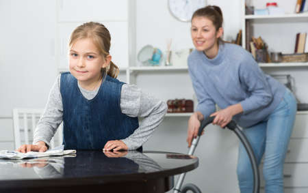 Mother and daughter cleans the house