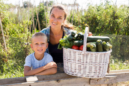 Woman and boy with gathered vegetables 版權商用圖片