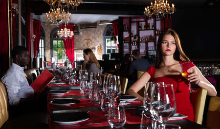 Elegant woman in red dress in luxury restaurante Banque d'images
