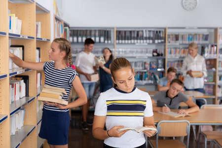 Schoolgirl holding books in library.