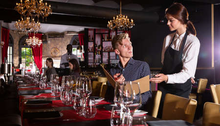 Attractive woman waiter receiving order from guest in fashionable restaurant Banque d'images