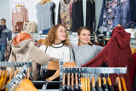 Women choosing new overcoat Stock fotó