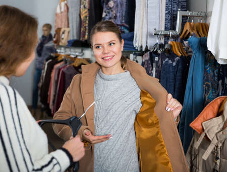 Woman trying new overcoat Stock fotó