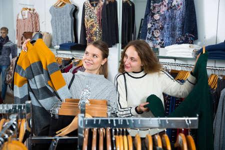 Women choosing cardigan in clothing shop
