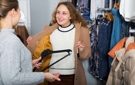 Women trying coat in clothing boutique
