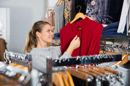 Girl holding red blouse on hanger Stock fotó