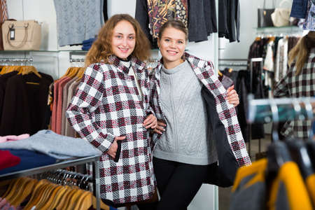 Women posing in overcoats in clothing boutique