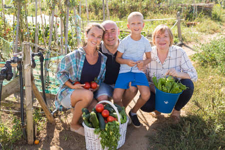 Family in garden with gathered vegetables