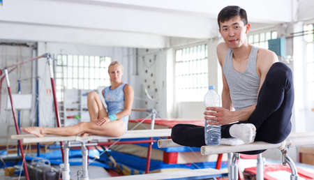 Couple sitting on top parallel bars 写真素材