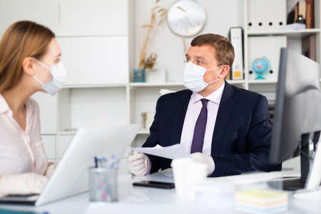 Businessman in face mask working with female assistant in office 写真素材
