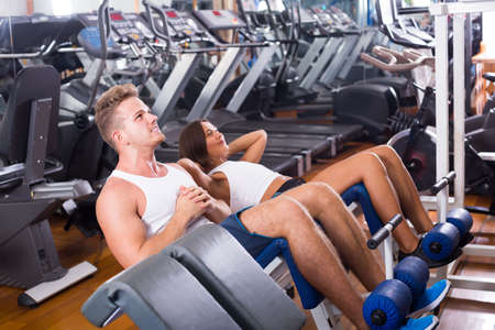 Well trained young cheerful man and woman training abdominal muscles in gym
