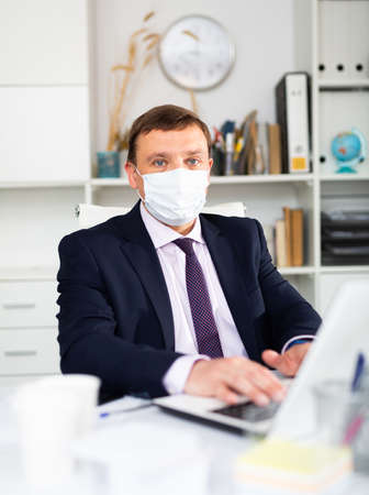 Entrepreneur in medical mask working with papers and laptop