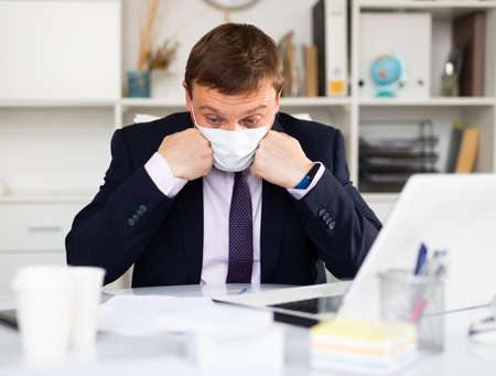 Puzzled businessman in medical mask looking at papers