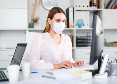 Female office worker in medical mask is having productive day at work in office 写真素材